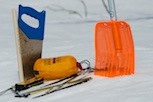 Emergency equipment for long mountain trips: spade, snow saw, wind sack, avalanche probe and transceiver.